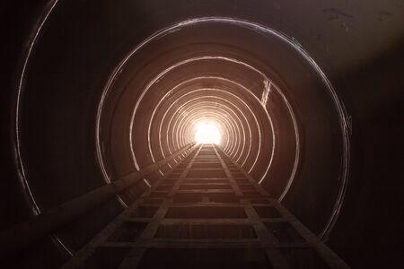 Duża stalowa rura tunelu ma czarny cień i światło na końcu tunelu.