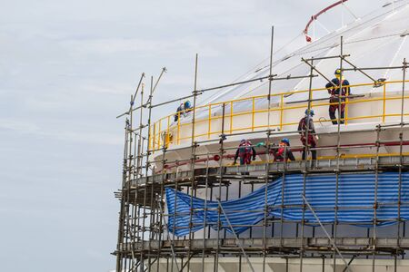 Construction workers installing scaffolding storage tank.
