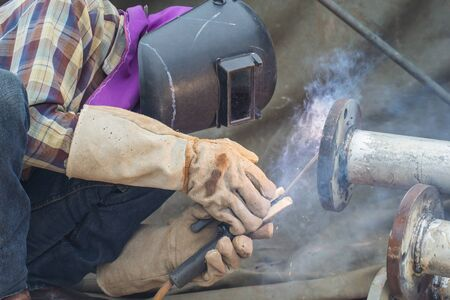 Male welder worker wearing protective clothing fixing Repair Pipeline welding smoke