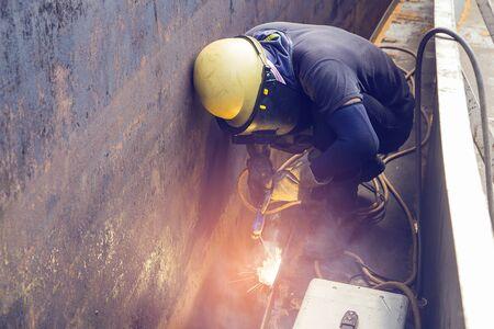 Mannelijke werknemer die beschermende kleding draagt, repareert de bouwrook van de opslagtankolie in besloten ruimtes. Stockfoto