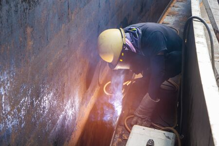 Male  worker wearing protective clothing repair  storage tank oil construction smoke inside confined spaces. Stock Photo