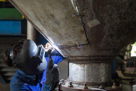 Worker welding repair stainless silo bottom tank using tig welder