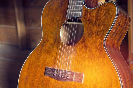 Gitara akustyczna opiera się na drewnianym stole w tle