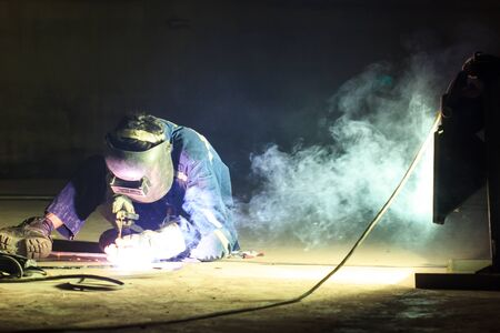 Male  worker wearing protective clothing repair  bottom plate storage tank industrial construction smoke spotlight inside confined spaces.