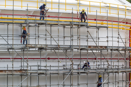 Chon Buri Thailand - July 16th, 2017: Construction workers installing scaffolding storage tank. Editorial