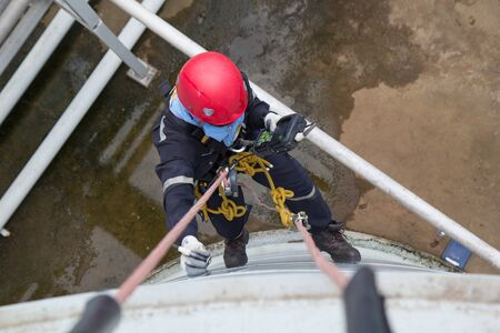 Top view male worker rope access  inspection of thickness storage tank industry below pipeline oil