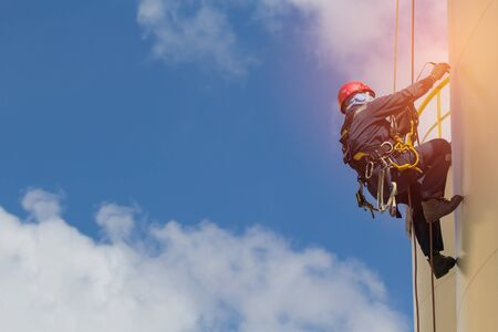 Male worker rope access inspection of thickness storage tank industry. 免版税图像