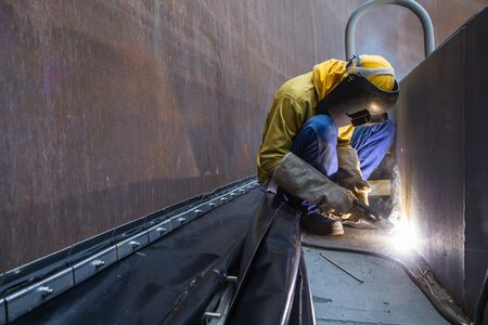 Male worker wearing protective clothing and repair welding patition plate industrial construction oil and gas or storage tank inside confined spaces.