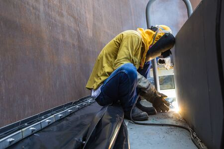 Male  worker wearing protective clothing and repair welding patition plate industrial construction oil and gas or  storage tank inside confined spaces. Stock Photo