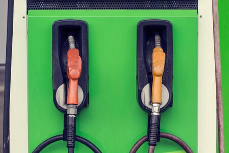 yellow and red petrol gas pump nozzles in a service station background green, Fuel nozzle in oil station Thailand Banque d'images