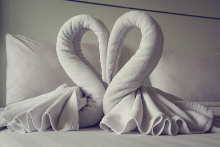 The swan towels on the bed in a hotel room.