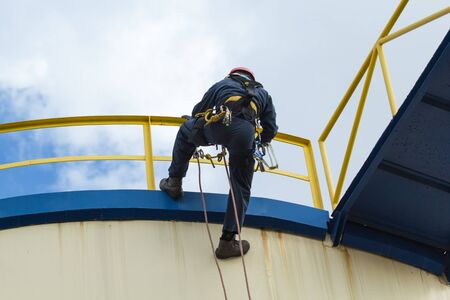 Male worker step across handrail roof plate rope access of inspection storage tank