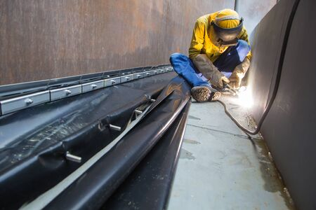 Male  worker wearing protective clothing and repair welding industrial construction oil and gas or  storage tank inside confined spaces. Banque d'images