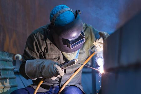 Male worker wearing protective clothing and repair plate tank oil welding industrial construction inside confined spaces.