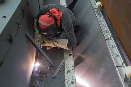 Top view Male  worker wearing protective clothing and repair welding industrial construction oil and gas or  storage tank inside confined spaces. Banque d'images