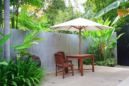 Wooden furniture covered by umbrella in garden , Thailand.