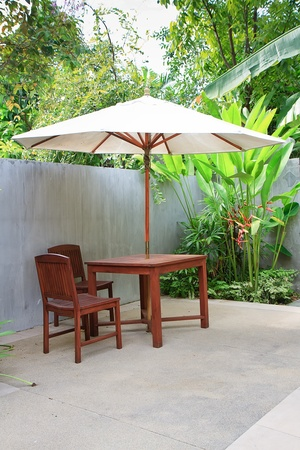 Wooden furniture covered by umbrella in garden , Thailand. Stock Photo - 10935933