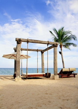 Beach beds among palm trees at perfect tropical coast Stock Photo - 10938354