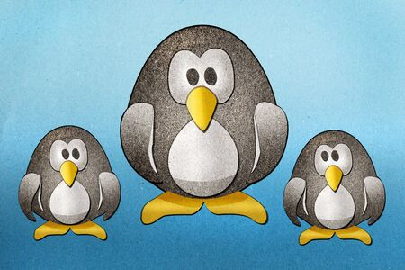 Penguins recycled paper craft on paper background photo