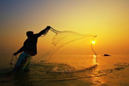 pescador: lanzando redes de pesca durante la puesta de sol