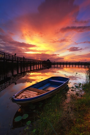 morn: Boat and wooden bridge with a beautiful sky.