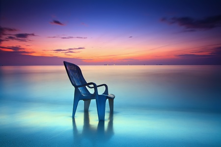 Einsamer Stuhl am Strand in der Früh.