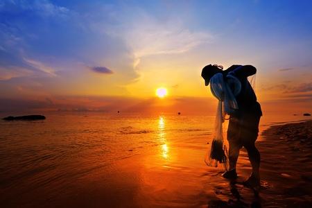 time flies: throwing fishing net during sunset Stock Photo