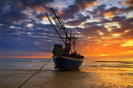 azur: Sunset over the ocean and fishing boat Stock Photo