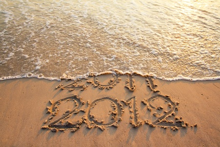 New Year 2012 is coming concept - inscription 2011 and 2012 on a beach sand, the wave is covering digits 2011 photo