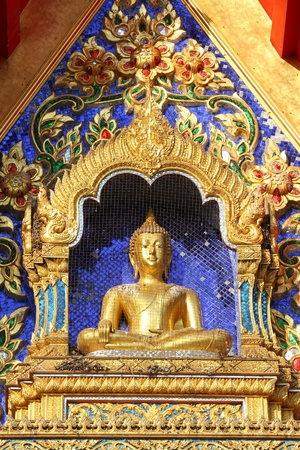 Golden Buddha statue in the temple wall. photo