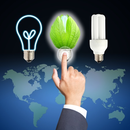 Business hand touch green light bulb concept of energy saving photo