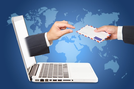 A business people hand holding air mail with  hand concept of receiving a message through a laptop photo