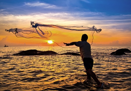 man fishing: lanzar una red de pesca durante la puesta de sol, tailandés
