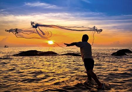 rzucanie sieci rybackiej podczas zachodu słońca, tajski Zdjęcie Seryjne