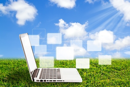 Laptop on grass and virtual buttons interface