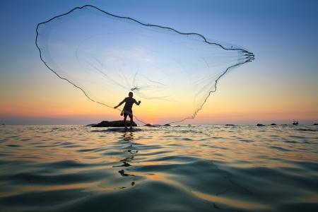 hombre pescando: lanzar una red de pesca durante el amanecer Foto de archivo
