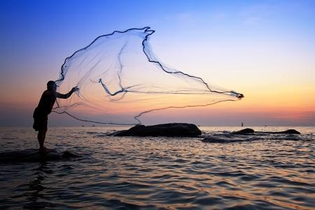 coger: lanzar una red de pesca durante el amanecer, Tailandia Foto de archivo