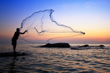 catch of fish: throwing fishing net during sunrise, Thailand