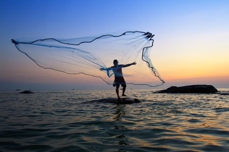 man fishing: lanzar una red de pesca durante el amanecer, Tailandia Foto de archivo