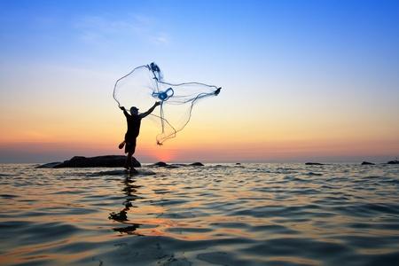 pescador: lanzar una red de pesca durante el amanecer, Tailandia Foto de archivo