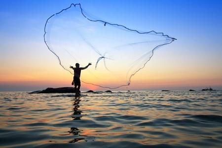 hombre pescando: lanzar una red de pesca durante el amanecer, Tailandia Foto de archivo