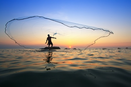 fishing catches: throwing fishing net during sunrise, Thailand