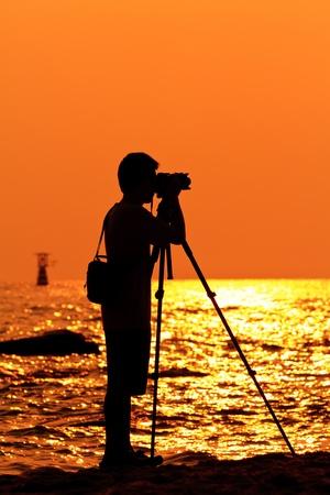 Photographer silhouette shooting sea outdoors photo