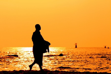 Silhouettes of monks on the beach,Hua Hin Thailand photo