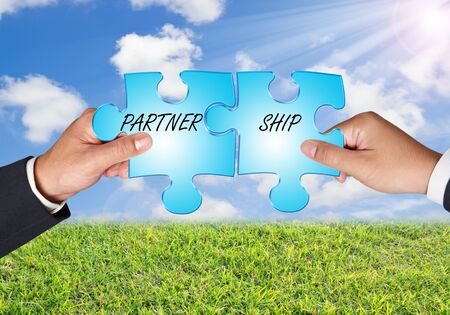 Business hands and puzzle partner ship on blue sky photo