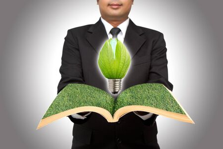 Businessman hold green light bulb from open book photo