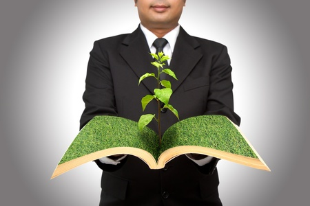 Businessman hold tree growing from open book photo