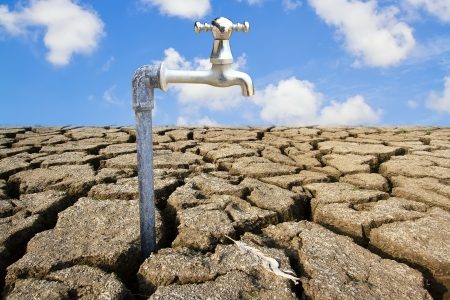 Water Faucet on Dry Soil Texture Stock Photo
