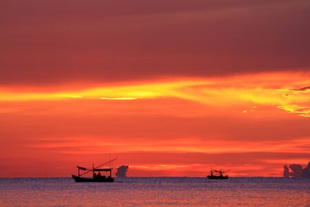 silhouette of fishermen with yellow and orange sun in the background photo