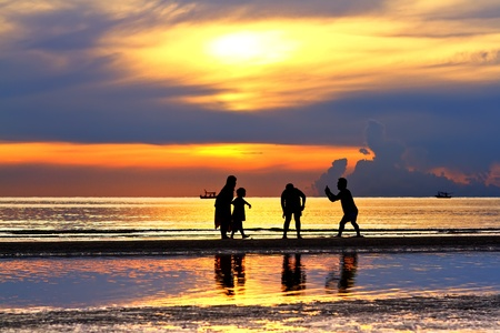 Silhouette of happy family  on beach  photo